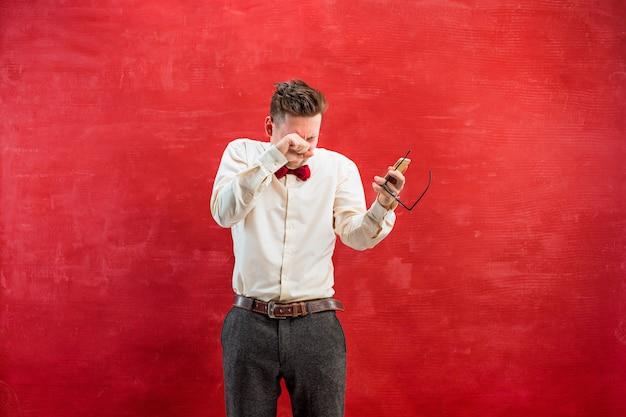 Портрет озадаченный мужчина разговаривает по телефону на красном