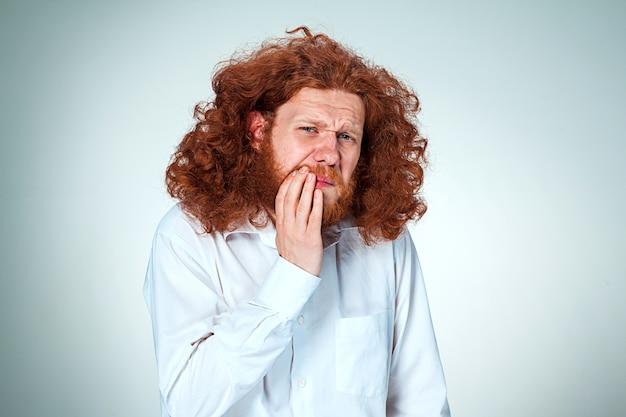 若い男は歯痛を持っています。
