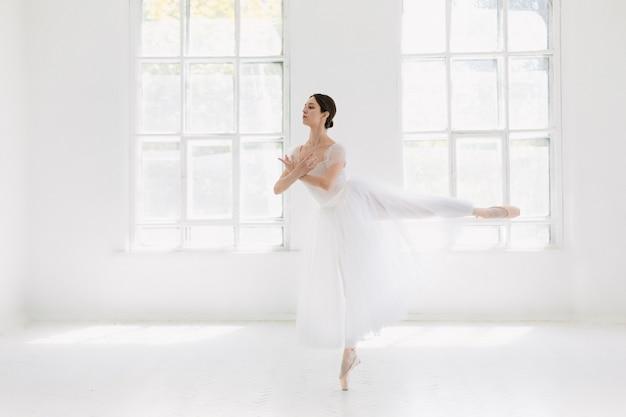 若くて信じられないほど美しいバレリーナが白いスタジオでポーズとダンスをしています