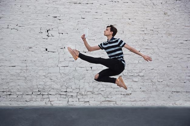 Прыгающий молодой бизнесмен перед зданиями, на бегу в прыжке высоко