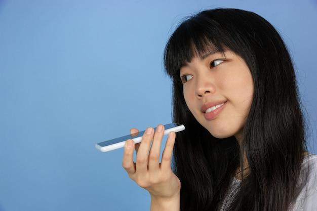 Портрет молодой азиатской женщины изолирован на голубом пространстве студии