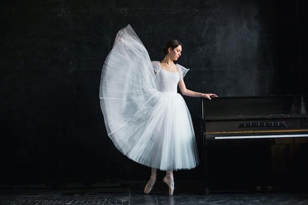 若くて信じられないほど美しいバレリーナが黒のスタジオでポーズをとっている
