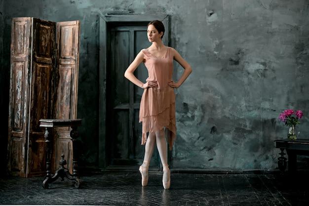 若くて信じられないほど美しいバレリーナが黒のスタジオでポーズとダンスをしています