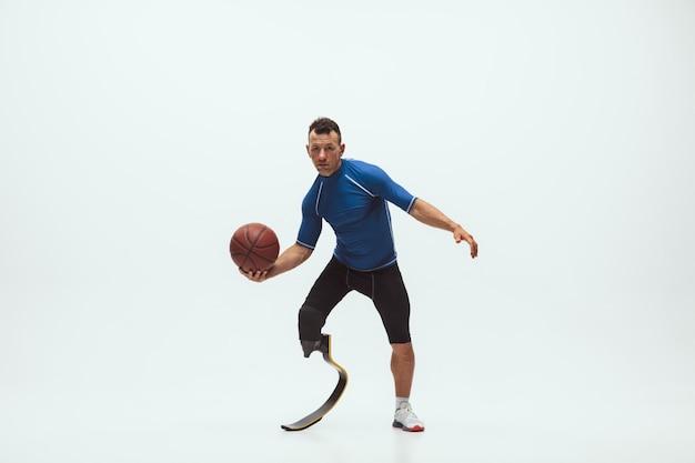 障害を持つアスリートまたは白いスタジオスペースで分離された切断患者。脚義足のトレーニングとスタジオでの練習を持つプロの男性バスケットボール選手。