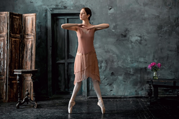 Молодая и невероятно красивая балерина позирует и танцует в черной студии
