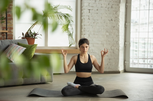 Спортивная молодая женщина берет уроки йоги онлайн и занимается дома