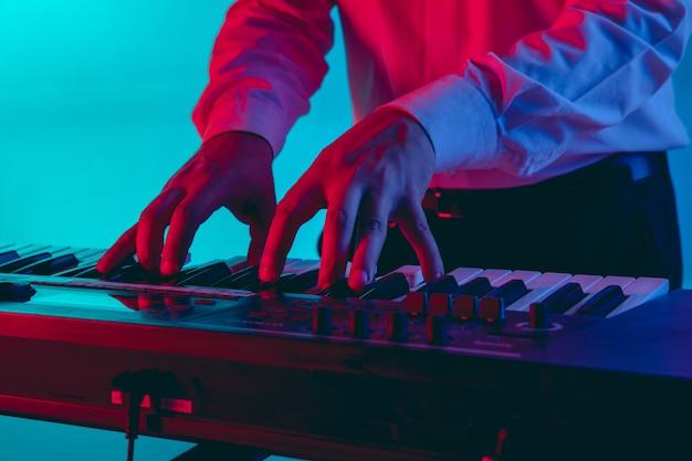 若い白人ミュージシャン、ネオンの光のグラデーションスペースで演奏するキーボード奏者。音楽、趣味、お祭りのコンセプト