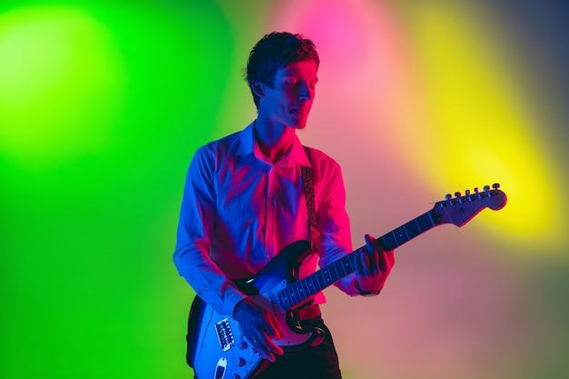 若い白人のミュージシャン、ギタリストがネオンの光のグラデーションスペースで演奏します。音楽、趣味、お祭りのコンセプト