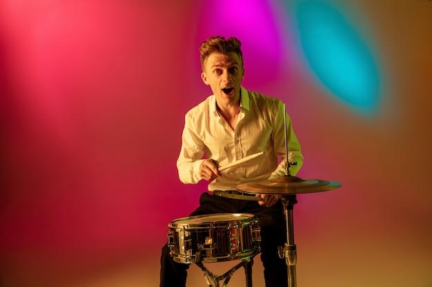ネオンの光のグラデーションスペースで遊ぶ若い白人ミュージシャン。音楽、趣味、お祭りのコンセプト