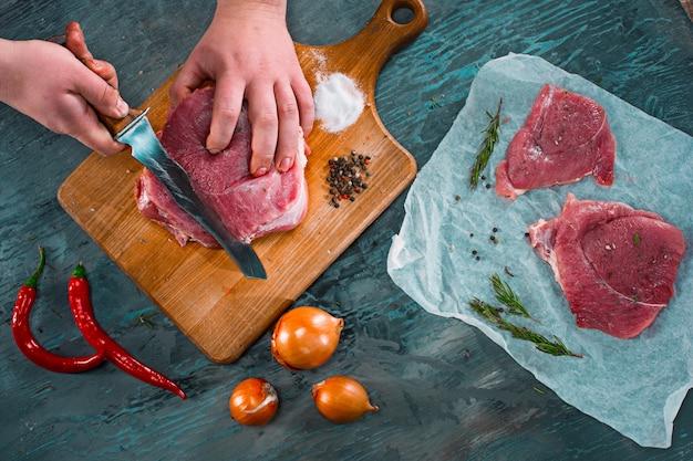 肉屋のキッチンで豚肉を切る