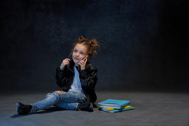 Маленькая девочка сидит с смартфон в студии