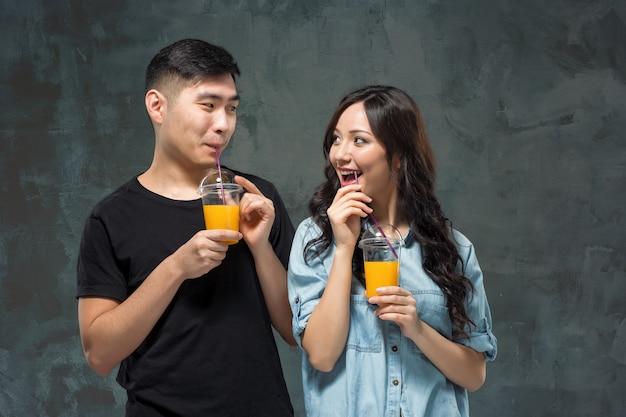 オレンジジュースのグラスを持つ若いアジアカップル