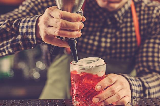 バーテンダーがバーのバーカウンターでアルコールカクテルを作る