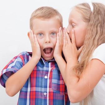 Девочка-подросток шепчет на ухо секретный мальчиков-подростков на белом