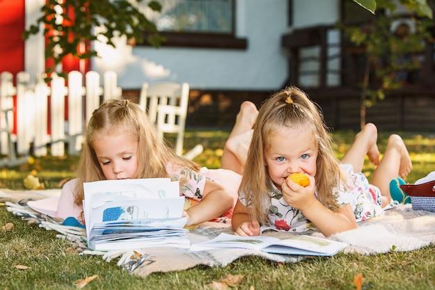 草の上の外の本を読んでかわいい小さなブロンドの女の子