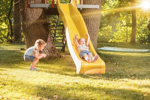 Счастливые маленькие девочки катятся с горки на детской площадке