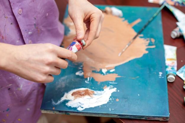 Крупный план рук с палитрой художника