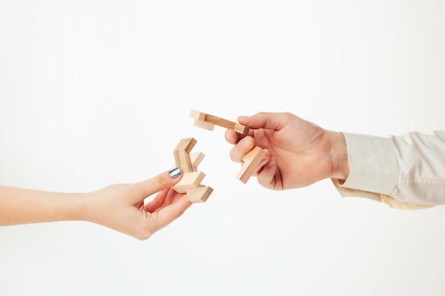白で隔離される手でおもちゃの木製パズル