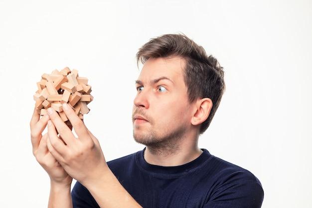 男は木製パズルで混乱しています。