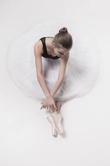 Балерина танцор сидит со скрещенными ногами