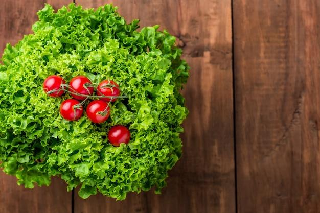 Салат из листьев салата и помидоров черри на деревянной стене
