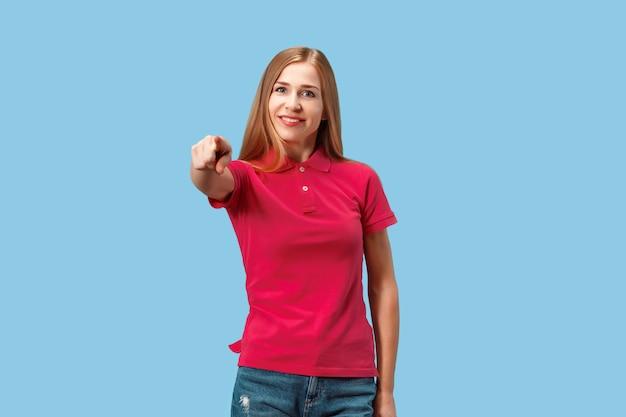 選んで注文します。笑顔のビジネスの女性はあなたを指して、あなたが欲しい、青いスタジオで半分の長さのクローズアップの肖像画