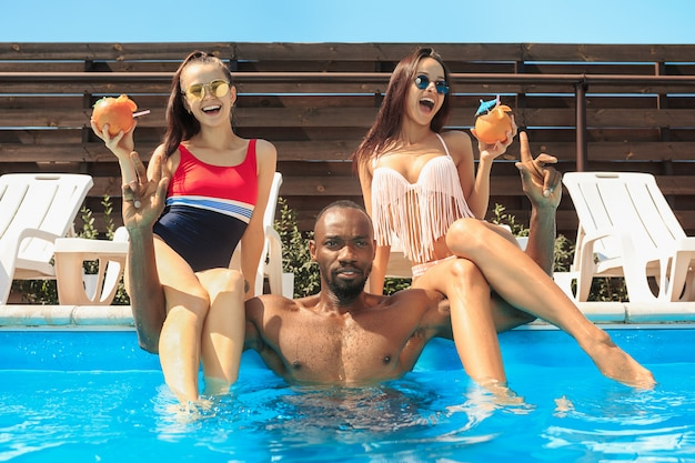Группа друзей, играющих и отдыхающих в бассейне во время летних каникул
