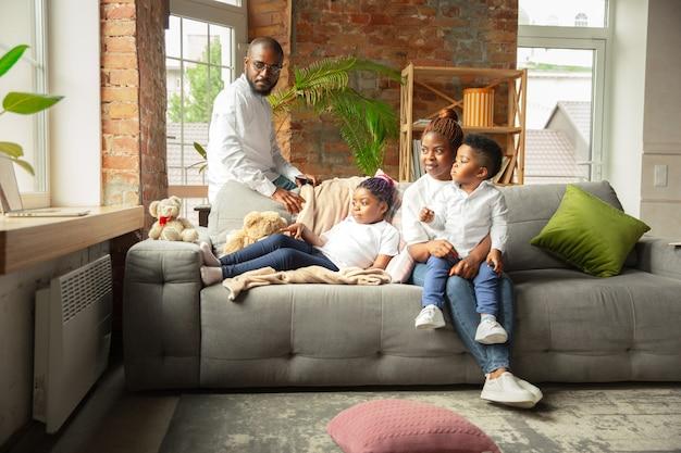 Молодая и жизнерадостная семья во время карантина, утепления, проводящего время вместе дома.