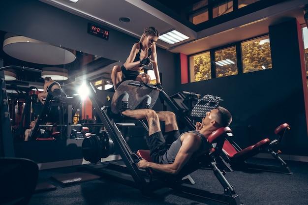 Спортивная (ый) мужчина и женщина с гантелями, тренировки и тренировки в тренажерном зале.