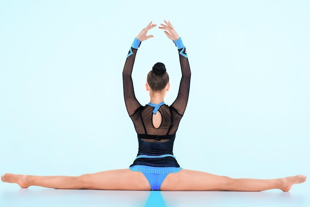 青い壁に体操ダンスをしている女の子