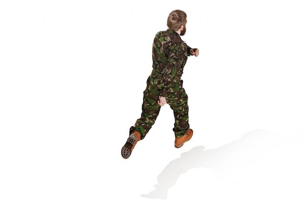 孤立した白いスタジオを実行している迷彩服を着ている若い陸軍兵士