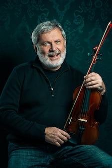 Старший музыкант играет на скрипке с палочкой на черном студии