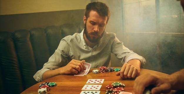 木製のテーブルに座っている男性の友人の側面写真。