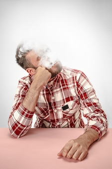 ハンサムな流行に敏感な男が自宅でタバコを吸って