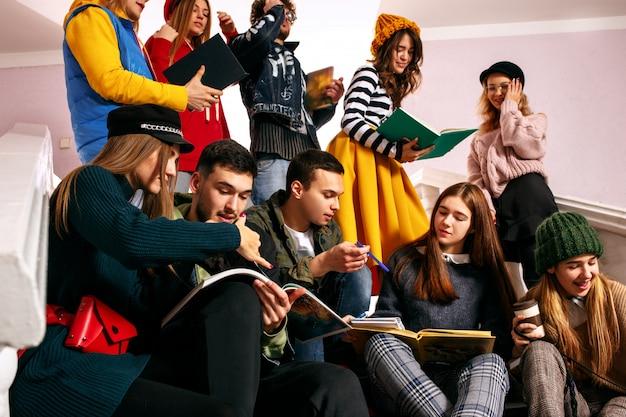 Группа веселых студентов сидит в аудитории перед уроком.