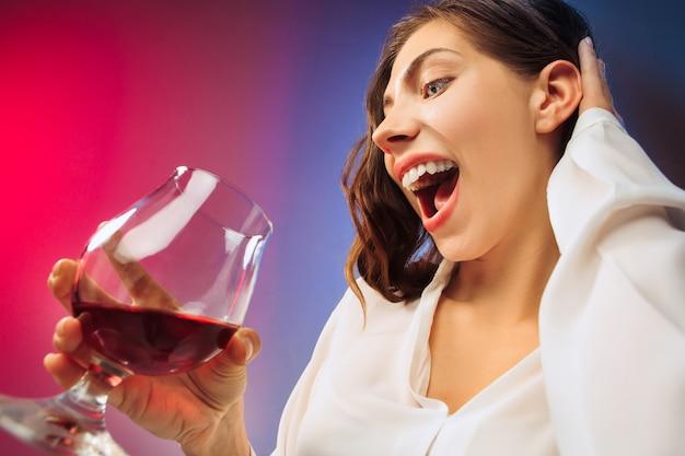 Удивленная молодая женщина в партийной одежде, позирующей со стаканом вина.