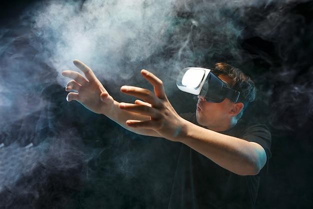 Человек в очках виртуальной реальности. концепция будущей технологии. черная студия дымчатый
