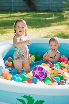 Две двухлетние маленькие девочки играют с игрушками в надувном бассейне в солнечный летний день