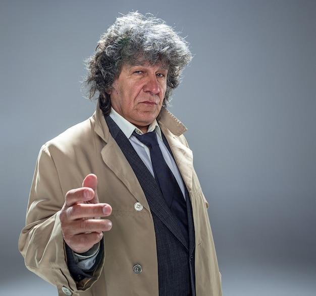 探偵またはマフィアのボスとしてマントを着た年配の男性。