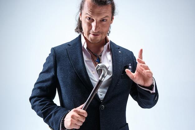 杖を持ったスーツを着た成熟したひげを生やした男。ブルースタジオに分離されました。