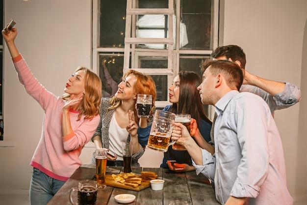 Группа друзей, наслаждаясь вечерними напитками с пивом на деревянный стол