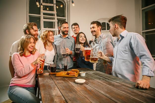 木製のテーブルにビールとイブニングドリンクを楽しんでいる友人のグループ