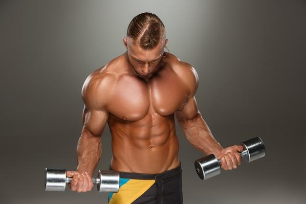 Привлекательный строитель мужского тела на сером