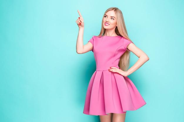 ポーズをとって、何かを提示するピンクのミニドレスで美しい若い女性を笑顔