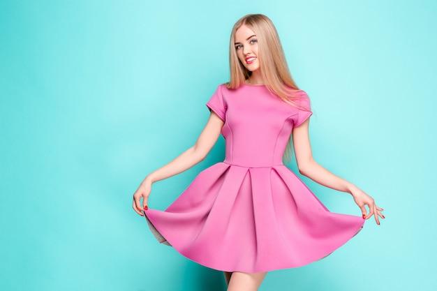 スタジオでポーズピンクのミニのドレスで美しい若い女性を笑顔