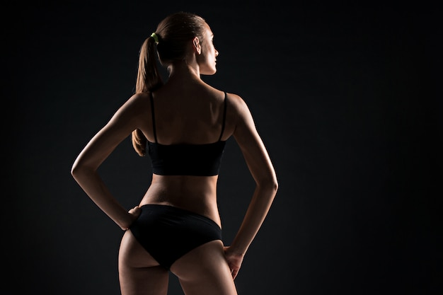 Задний взгляд мышечного спортсмена молодой женщины представляя на сером цвете