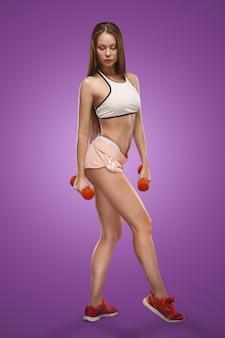 Мускулистые спортсменки молодая женщина позирует на сиреневом пространстве с гантелями