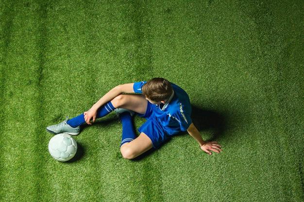 Мальчик футболист, сидя на зеленой траве