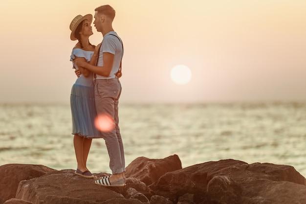 幸せな若いロマンチックなカップルはビーチでリラックスして夕日を見て