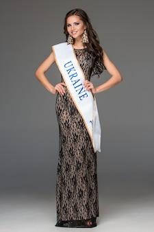 Красивая молодая брюнетка женщина с распущенными волосами, позирует в длинное платье.